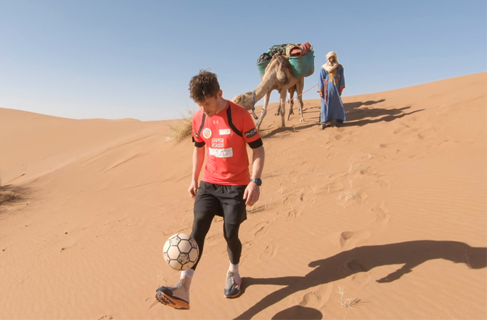 John-Farnworth-with-camel-in-background-practising-for-farthest-distance-covered-juggling-a-football-in-an-hour.jpg
